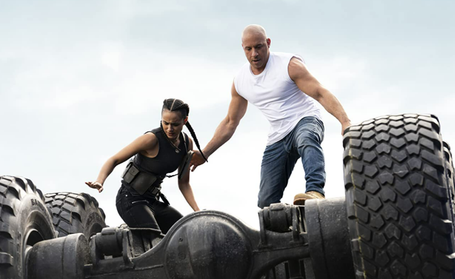 A bald man and a woman with her hair in braids stand on the underside of a truck, ready to jump