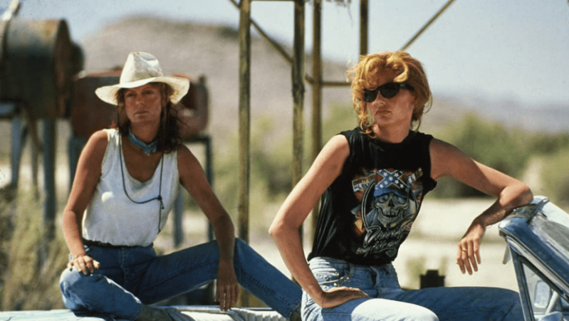 Two women, one wearing sunglasses and the other in a cowboy hat, sit atop a convertible with the top down.