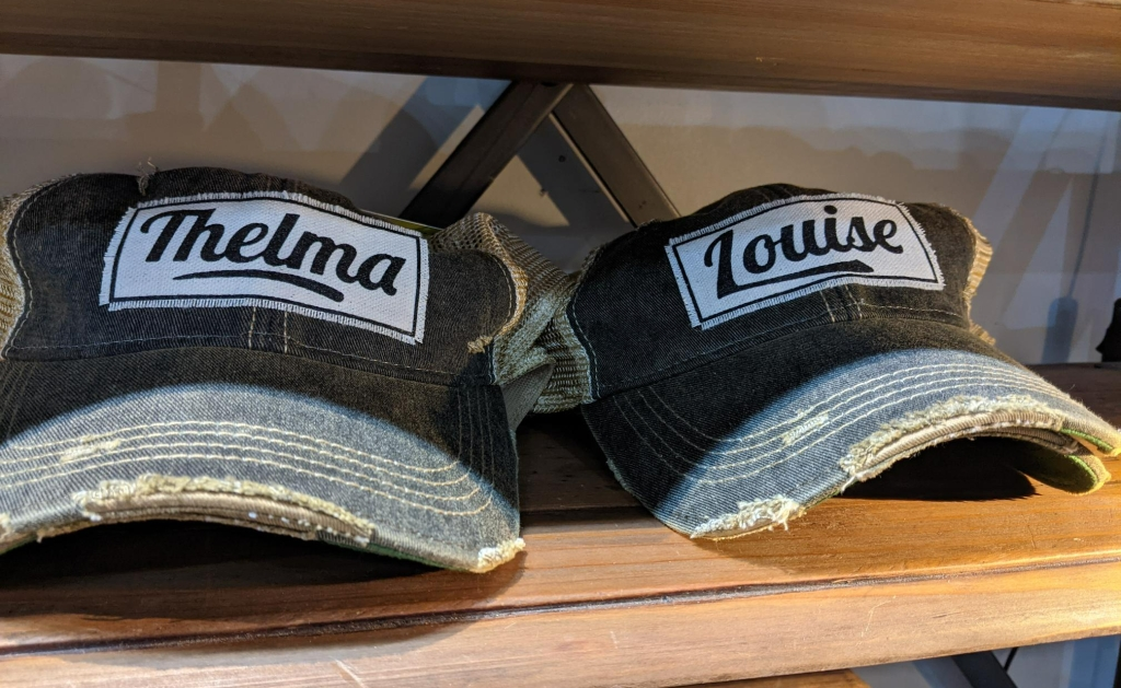 """Trucker-style hats with embroidered labels, one saying """"Thelma"""" and the other """"Louise"""""""