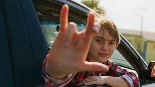 """A teenage girl waves out of a car's passenger window, saying, """"I Love You"""" in American Sign Language"""