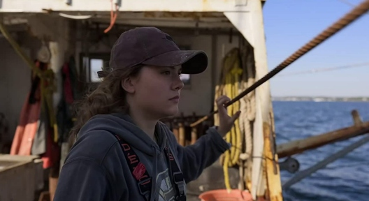 A young woman stands on the deck of a fishing trawler and looks out at sea. She has long auburn hair and wears a ballcap, a hoodie, and coveralls.