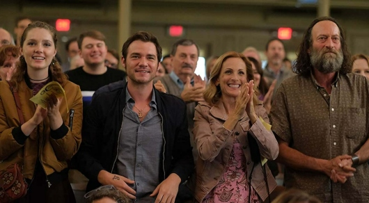 A twentysomething woman, a twentysomething man, and a woman and a man in their fifties stand and applaud proudly at a concert.
