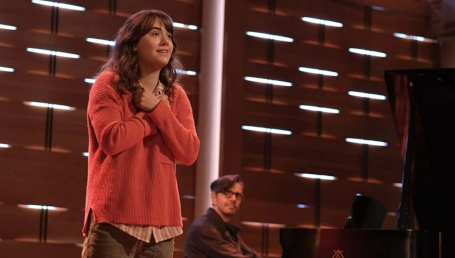 A teenage girl with auburn hair and a red sweater, her arms crossed over her chest, sings onstage as a man accompanies her on the piano.
