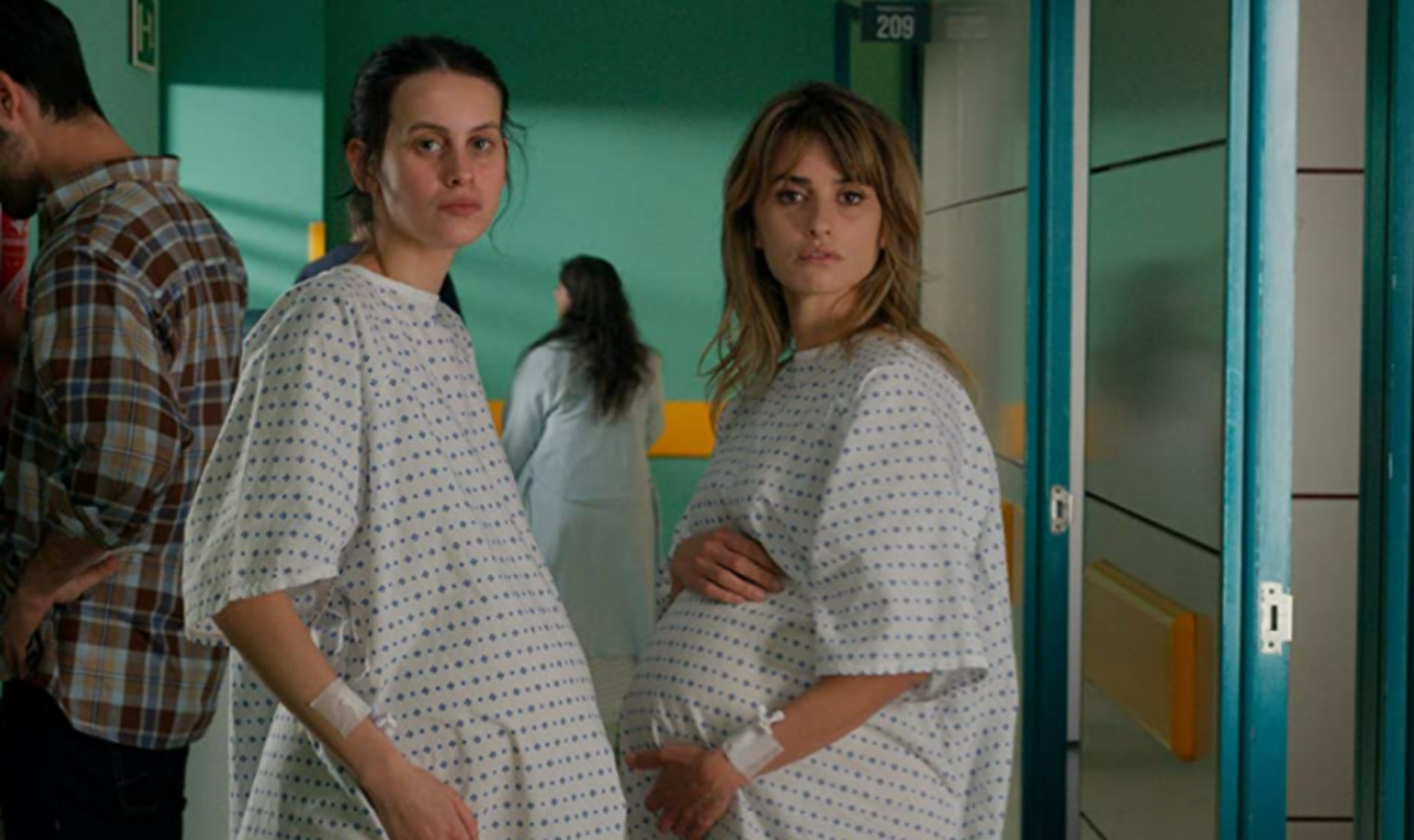 Two pregnant women, one in her forties and another about half her age, in a maternity ward.